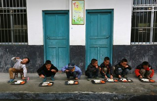 Students have lunch outdoors at a primary school in Tongguan village, Liping county, Guizhou province, November 24, 2014