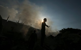 A Palestinian standing atop the remains of a house, which witnesses said was destroyed in an Israeli air strike, reacts as smoke rises in Gaza City July 31, 2014
