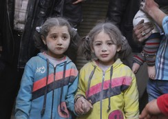 Girls who survived what activists said was a ground-to-ground missile attack by forces of Syria's President Assad, hold hands at Aleppo's Bab al-Hadeed district