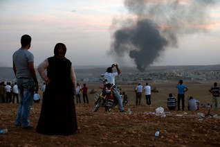 Smoke rises in the Syrian town of Kobani as Turkish Kurds watch near the Mursitpinar border crossing on the Turkish-Syrian border in the southeastern town of Suruc