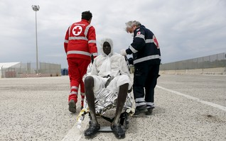 Red Cross members help a migrant after he disembarked in the Sicilian harbour of Augusta, Italy, May 31, 2015