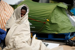 A migrant from Eritrea covers his face as he sits near tents in a make-shift camp