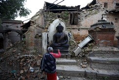 A woman offers daily prayers at the statue of Lord Buddha that was damaged during the earthquake in Bhaktapur