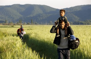 An Afghan immigrant walks through a field towards Macedonia
