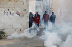 Protesters take cover from tear gas fired by riot police in the village of Bilad Al Qadeem south of Manama