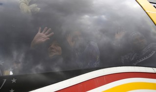 Palestinians returning to Gaza wave as they look out a bus window at the Rafah border crossing between Egypt and southern Gaza Strip November 26, 2014