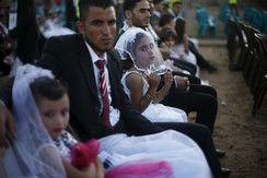 Girls accompany grooms as they sit separate from the brides during a mass wedding for 150 couples in Beit Lahiya town in the northern Gaza Strip