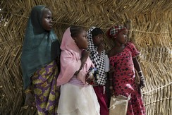 Girls watch soldiers from Niger and Chad in the recently retaken town of Damasak