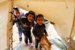Syrian refugee children play in front of their family tent which was damaged after a heavy snowstorm at Al Zaatari refugee camp in the Jordanian city of Mafraq, near the border with Syria