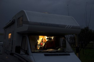 A humanitarian worker sits inside a truck on a field where migrants cross the border with Croatia near the village of Berkasovo, Serbia, October 16, 2015.