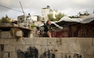 Palestinian man plays with his son outside their damaged house in Biet Lahiya town in the northern Gaza Strip