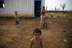 A family is pictured outside their house in Rio Pardo next to Bom Futuro National Forest, in the district of Porto Velho, Rondonia State, Brazil