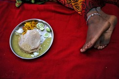 A plate of food is pictured on the bed of a woman who underwent sterilisation surgery at a government mass sterilisation camp, as she rests inside a hospital, India, 15, 2014