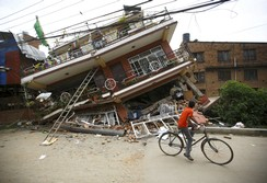 Boy riding a bicycle looks at a collapsed house after Saturday's earthquake, in Kathmandu