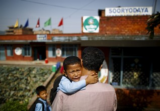 Saksham Karmacharya, 4, cries while hugging his father Birendra Karmacharya saying that he does not wants to go to school while being carried towards his school, a month after the April 25 earthquake in Bhaktapur, Nepal May 31, 2015