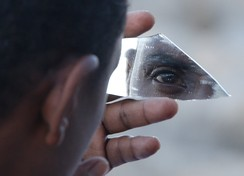 A migrant uses a piece of glass as a mirror as he stands on the rocks of the seawall at the Saint Ludovic border crossing on the Mediterranean Sea between Vintimille, Italy and Menton, France, June 17, 2015