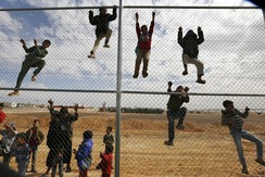 Syrian refugee children climb on a fence to watch a football training workshop in a refugee camp to provide Syrian and Jordanian trainers with football training skills, at Azraq refugee camp near Al Azraq city, Jordan