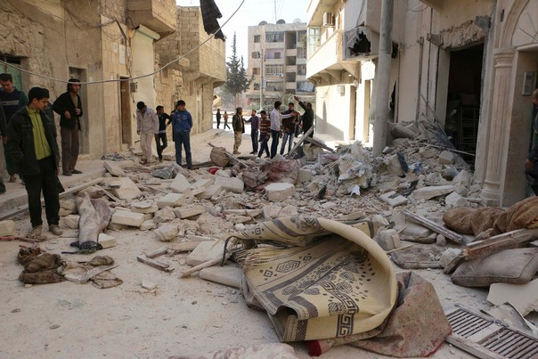 People stand at a damaged street after what activists said was an airstrike by forces loyal to Syrian President Bashar al-Assad in Masaken Hanano in Aleppo, Syria, February 14, 2014. REUTERS/Hosam Katan