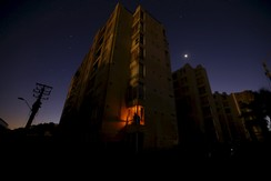 A resident looks out from his flat during a blackout after an earthquake hit areas of central Chile