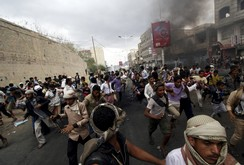 Anti-Houthi protesters run as pro-Houthi police troopers open fire in the air to disperse them in Yemen's southwestern city of Taiz