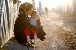 A Kurdish refugee woman from the Syrian town of Kobani holds a child in a camp in the southeastern town of Suruc, Sanliurfa province October 25, 2014