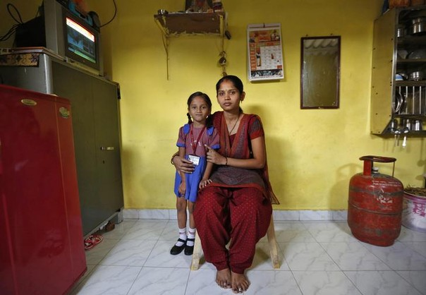 Sulochna Mohan Sawant, 23, poses with her five-year-old daughter Shamika Sawant inside their home in Mumbai, India February 13, 2014.   Sulochna, who works as a maid, wanted to become a doctor when she was a child. However, she could only study until the age of 14.   Sulochna wants her daughter to become a teacher, and Shamika shares her mother's dream.