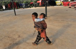 A Kokang boy carries his sister at a refugee camp, at China's border town with Myanmar, Nansan
