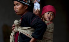 A woman carries her baby at a refugee camp at Myanmar's border town with China, in Kokang