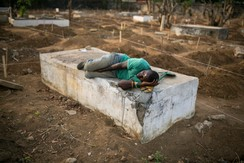 A grave digger sleeps near the graves of Ebola victims at a cemetery in Freetown, December 17, 2014