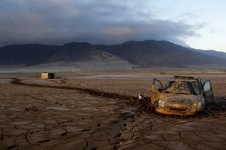A vehicle partially submerged in dry mud is pictured in an area that was hit by floods at Chanaral town, April 8, 2015. Chile was hit by heavy rains and floods at the end of March. REUTERS/Ivan Alvarado