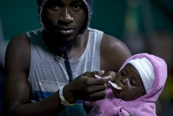 Foreign man feeds his child after xenophobia driven violence, S. Africa