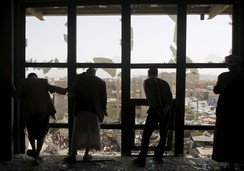 People look at a marketplace after it was hit by a Saudi-led air strike in Yemen's capital Sanaa