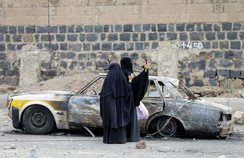 Woman takes photos with her mobile phone at the site of a Saudi-led air strike in Yemen's capital Sanaa