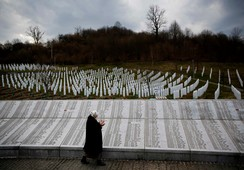 Fadila Efendic prays near memorial plaques at the Potocari genocide memorial centre near Srebrenica