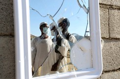 Workers wearing medical masks are reflected in a mirror in Taif November 1, 2014