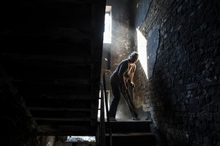 A woman cleans up debris inside a building that was recently shelled in Donetsk, eastern Ukraine, September 17, 2014