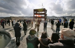 People observe a moment of silence to mark the anniversary of the 2011 Japan earthquake and tsunami.