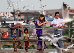 Children selling food for seagulls stand next to a couple feeding the birds at Botahtaung Jetty in Yangon, Myanmar