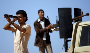 Libya Dawn fighter uses a monocoular to look at Islamic State (IS) militant positions near Sirte