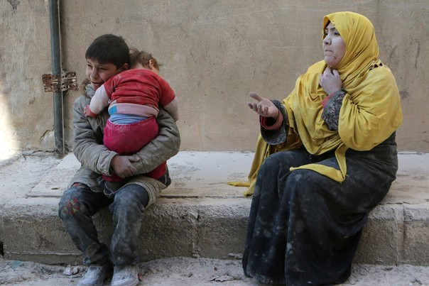 A boy holds his baby sister who was saved from under rubble, after what activists said was an airstrike by forces loyal to Syrian President Bashar al-Assad in Masaken Hanano in Aleppo, Syria, February 14, 2014. REUTERS/Hosam Katan