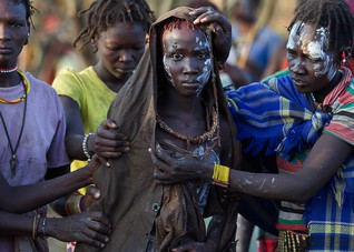 A Pokot girl, covered in animal skins, walks to a place where she will rest after being circumcised in a tribal ritual in a village about 80 kilometres from the town of Marigat in Baringo County, October 16, 2014