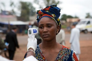 Health worker checks the temperature of a woman entering Mali from Guinea at the border in Kouremale