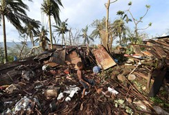 A boy called Samuel kicks a ball as his father Phillip searches through the ruins of their home which was destroyed by Cyclone Pam in Port Vila