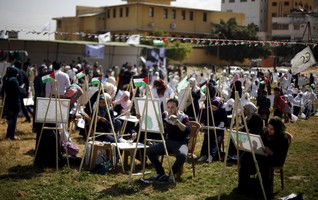 Palestinian artists paint artworks during an activity marking Land Day in Gaza City