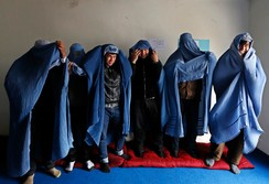 Male Afghan women's rights activist pose for media as they wear burqas to show their solidarity to Afghan women ahead of International Women's Day in Kabul