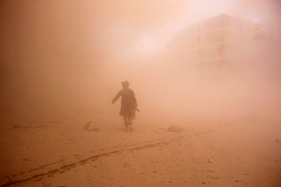 A rebel fighter runs through dust towards an area damaged by what activists said were barrel bombs dropped by warplanes loyal to Syria's President Assad in Aleppo