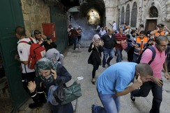 Palestinian protesters run away as Israeli police throw a stun grenade in Jerusalem's Old City