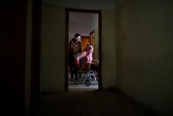 Brother of 15-year-old Palestinian girl Manar Al-Shinbari pushes her in a wheelchair inside an apartment in Jabaliya refugee camp