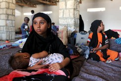 Girl holds a baby in a temporary shelter after fleeing violence in Yemen, at the port town Bosasso in Somalia's Puntland