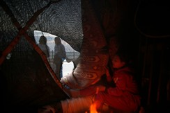 A Palestinian girl warms herself by a fire in a makeshift shelter in Gaza City